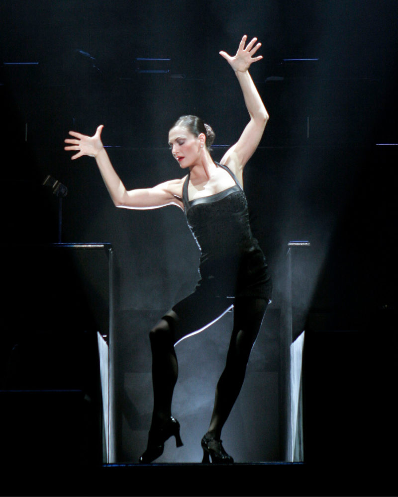 The actress playing Velma Kelly in CHICAGO strikes a signature Fosse-style pose with spread jazz hands above her head and on toe pointed at the top of the stairs as she makes her entrance.